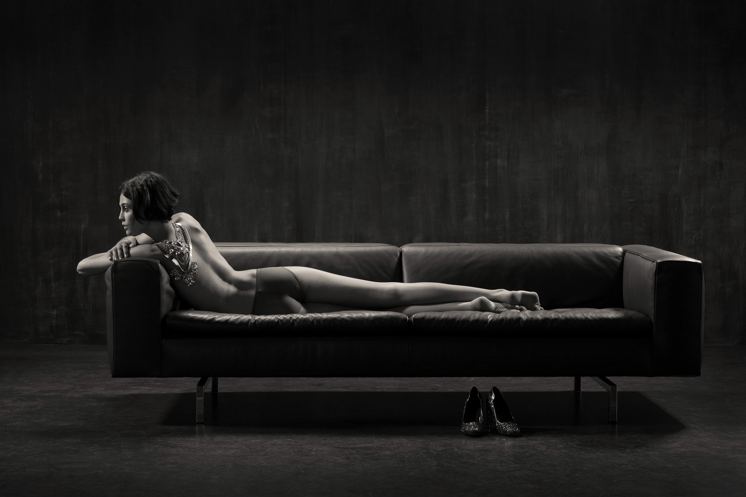 Nude model is stretched out on a leather seat. Black and white. Campaign image for seat manufacturer Stolz
